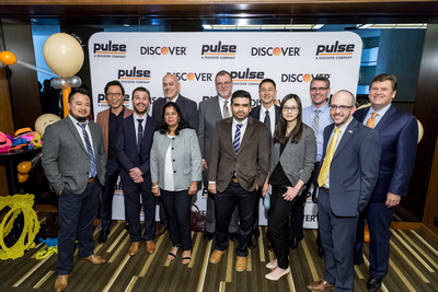 People standing in front of PULSE Discover backdrop at awards ceremony